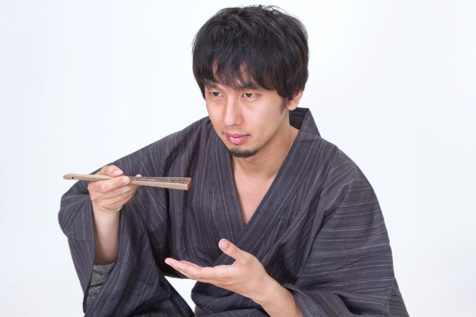 扇子を使って何かを食べる浴衣男子