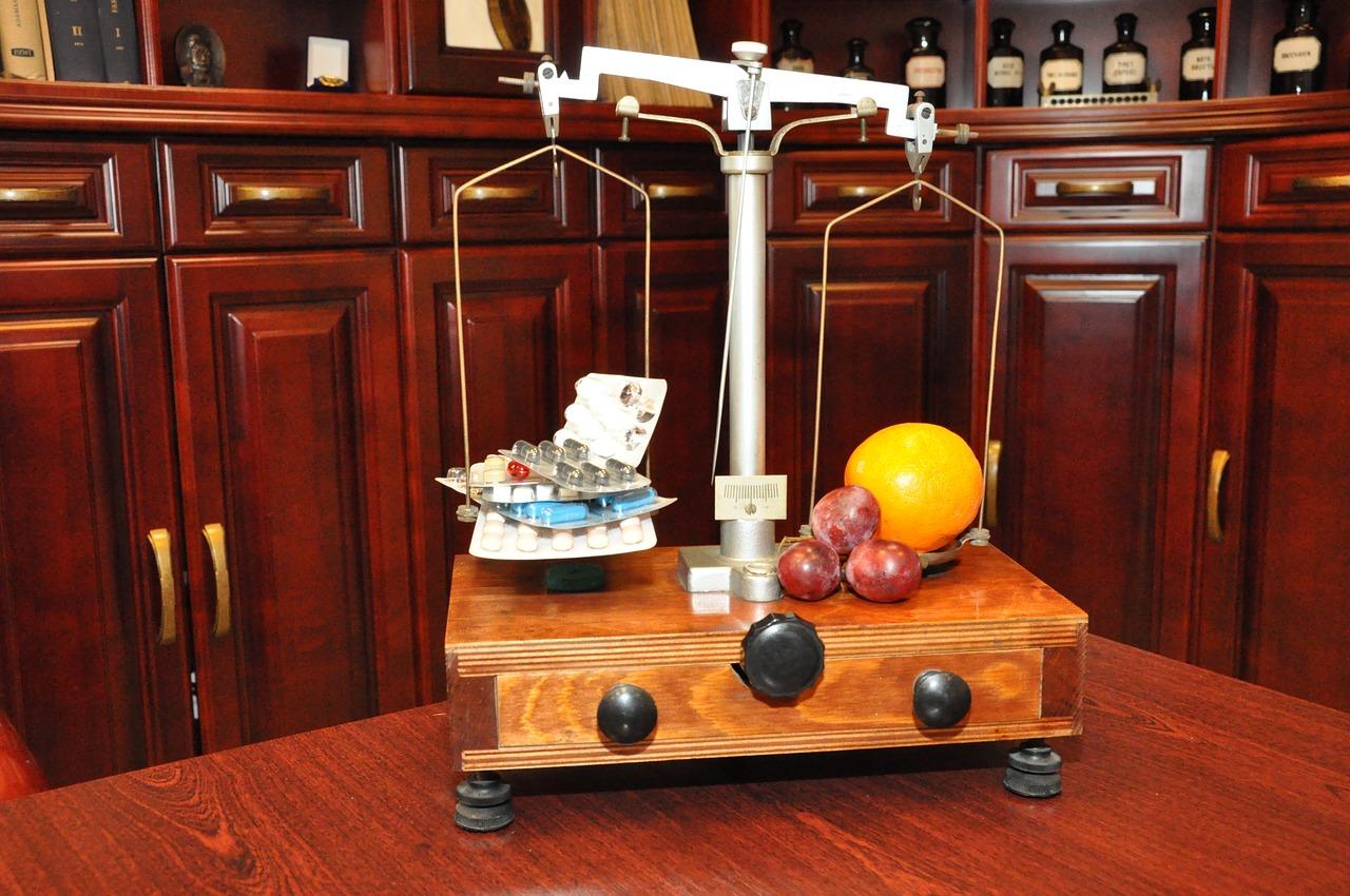 サプリメントと果物を天秤で量る